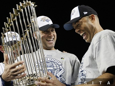 Two members of the core four, Derek Jeter and Mariano Rivera, hold the World Series Trophy