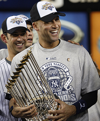 New York Yankees player Jeter celebrates as he holds the World Series trophy after the Yankees defeated the Philadelphia Phillies in New York